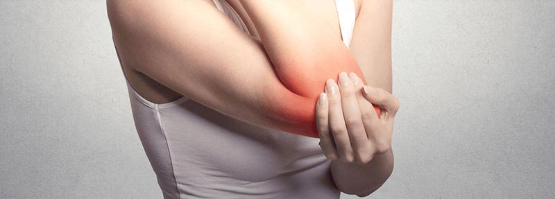 Frau hält sich am schmerzhaften Ellbogen