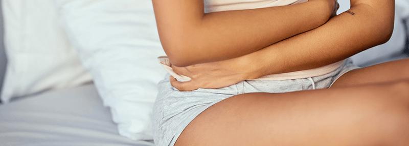 Frau hält sich schmerzhaft den Bauch
